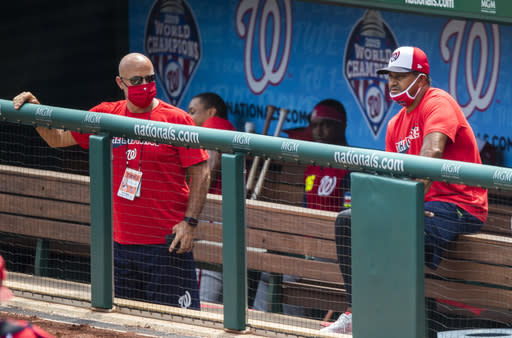 FILE - In this Sunday, Aug. 2, 2020, file photo, Washington Nationals manager Dave Martinez, right, with General Manager Mike Rizzo, left, watch from the dugout a baseball intrasquad game at Nationals Park in Washington. For the second season in a row, manager Dave Martinezs Washington Nationals got off to a 19-31 start. This time, there were not enough games to dig themselves out of that hole. (AP Photo/Manuel Balce Ceneta, File)