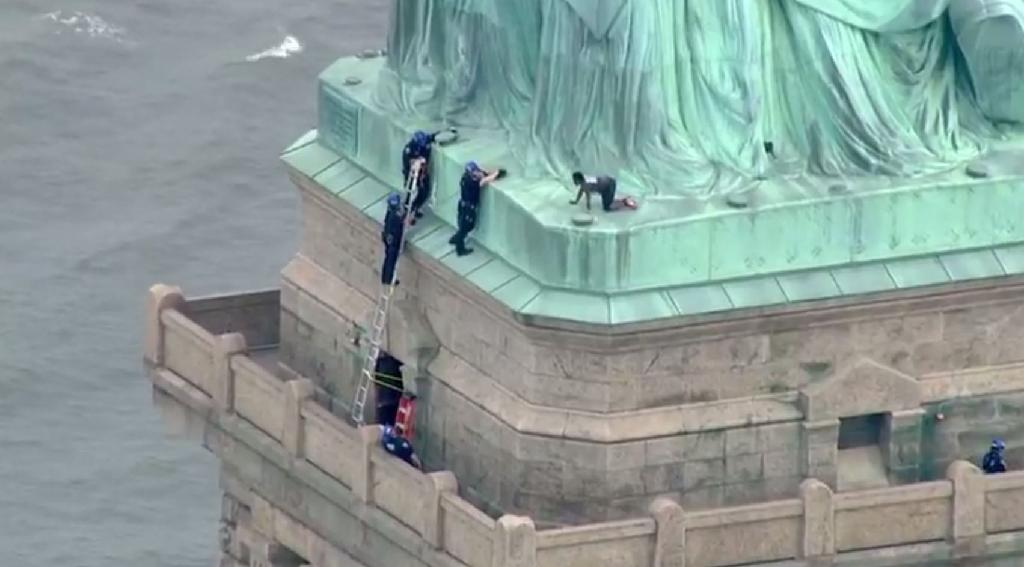 This screengrab shows police talking to Therese Okoumou, a woman who climbed to the base of the Statue of Liberty to protest the separation of migrant children from their family members