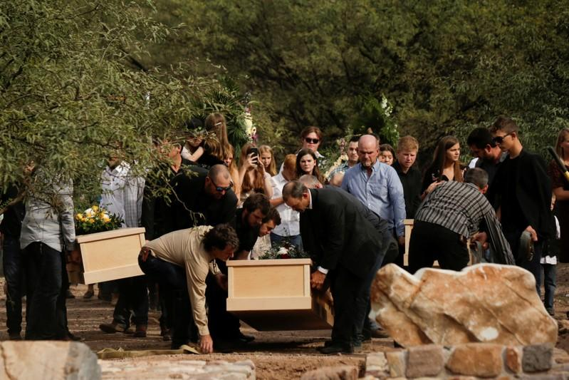 Relatives carry the remains of Dawna Ray Langford and her sons Trevor, Rogan, who were killed by unknown assailants, to be buried at the cemetery in La Mora