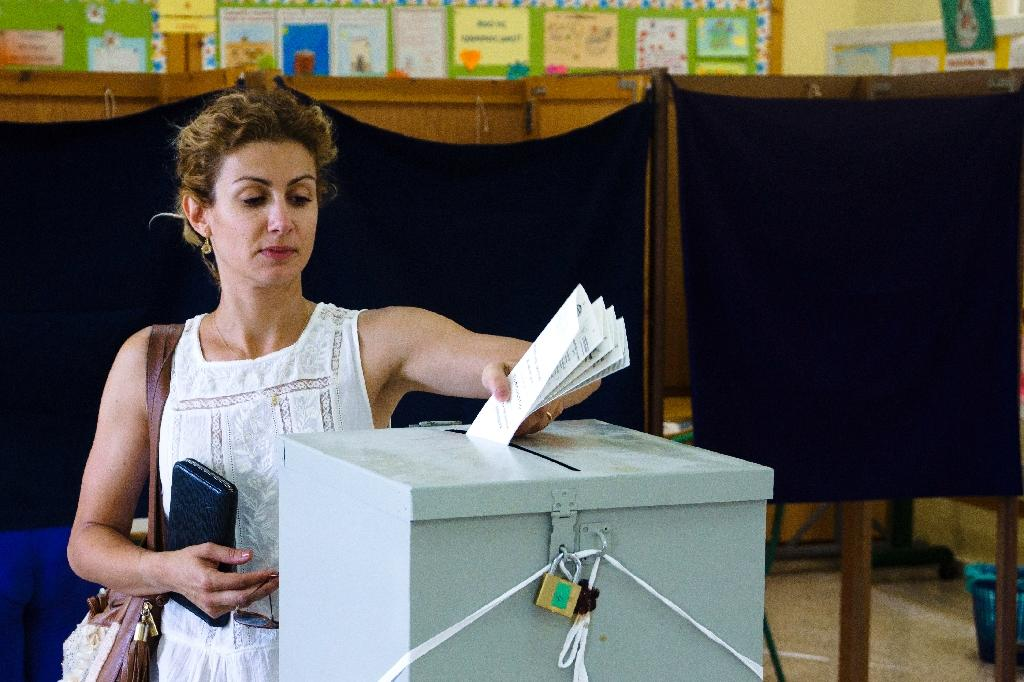 A woman casts her ballot for the parliamentary elections at a polling station in the capital Nicosia on May 22, 2016 (AFP Photo/Iakovos Hatzistavrou)