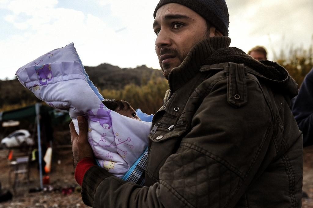 A migrant holding his baby arrives along with other migrants and refugees on the Greek island of Lesbos on November 10, 2015, after crossing the Aegean Sea from Turkey (AFP Photo/Aris Messinis)