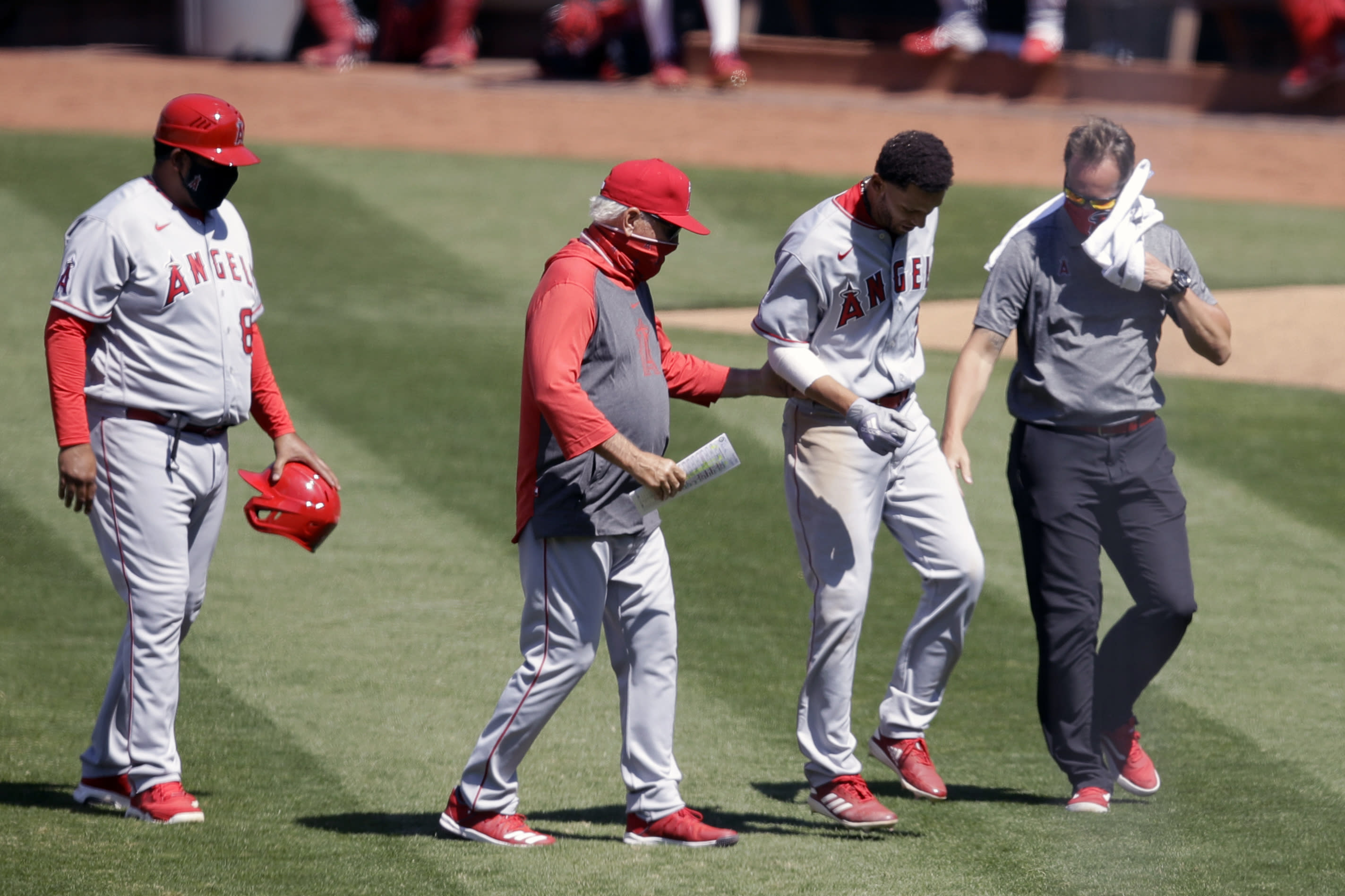 Los Angeles Angels' Andrelton Simmons, second from right, is helped off the field by manager Joe Maddon, second from left, after an injury during the ninth inning of a baseball game against the Oakland Athletics, Monday, July 27, 2020, in Oakland, Calif. (AP Photo/Ben Margot)