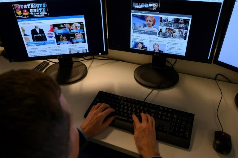 """AFP journalist looks at sites that are part of Christopher Blair's """"America's Last Line of Defense"""" network which runs eight websites and five Facebook pages (AFP Photo/Eric BARADAT)"""