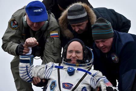 Ground personnel help U.S. astronaut Scott Kelly to get out of a Soyuz capsule shortly after landing near the town of Dzhezkazgan (Zhezkazgan), Kazakhstan, March 2, 2016. REUTERS/Kirill Kudryavtsev/Pool