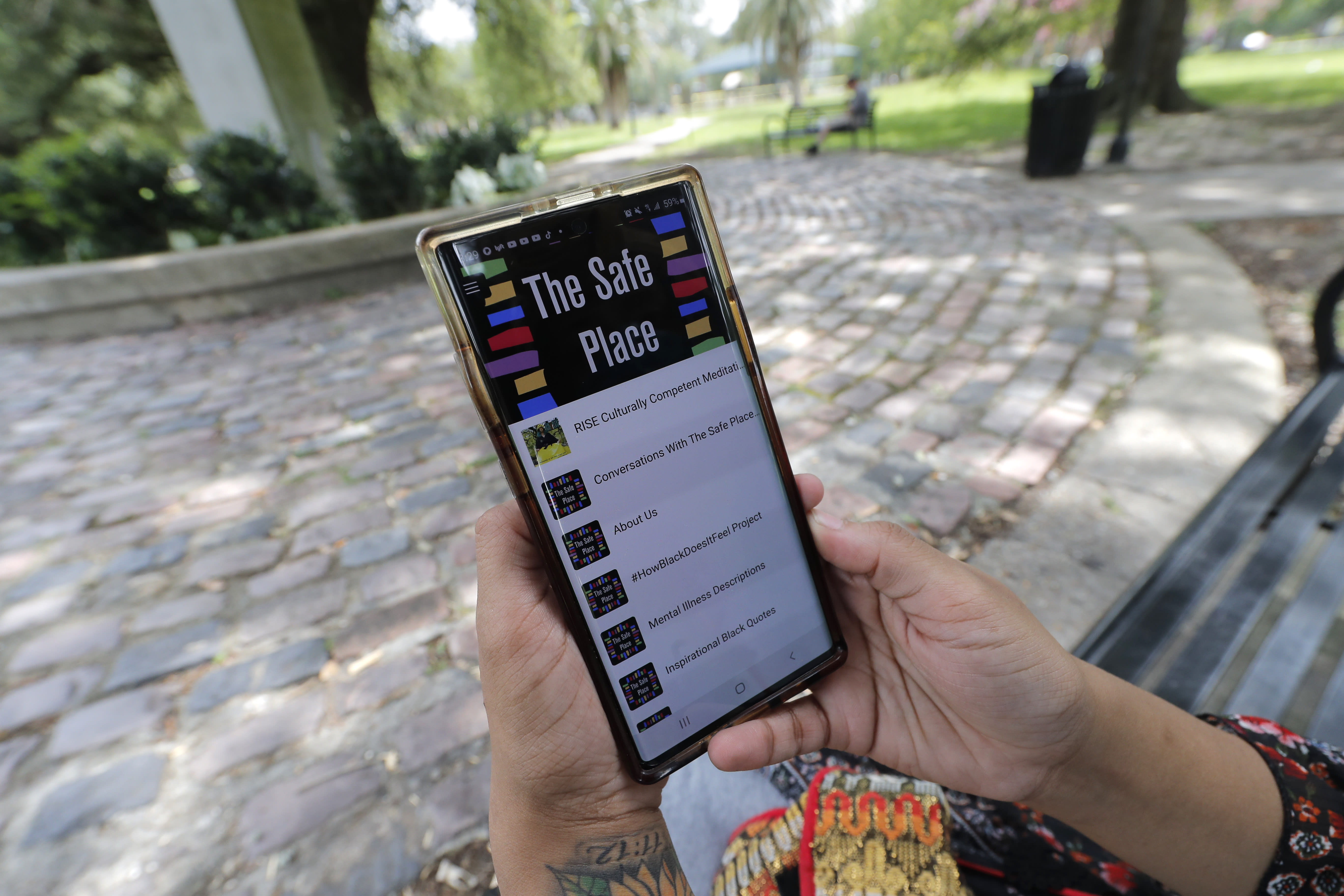 Jasmin Pierre poses for a photo with her smartphone app, in New Orleans, Thursday, July 2, 2020. Pierre, who survived multiple suicide attempts, doesn't want people struggling alone. She created The Safe Place, a free Black-oriented mental health app that's seen more signups during the pandemic. (AP Photo/Gerald Herbert)