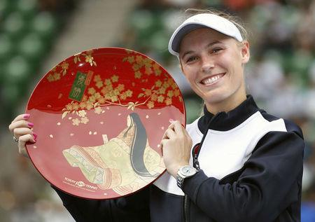 Caroline Wozniacki of Denmark holds the winning plate after winning the final match at Pan Pacific Open Women's tennis tournament in Tokyo
