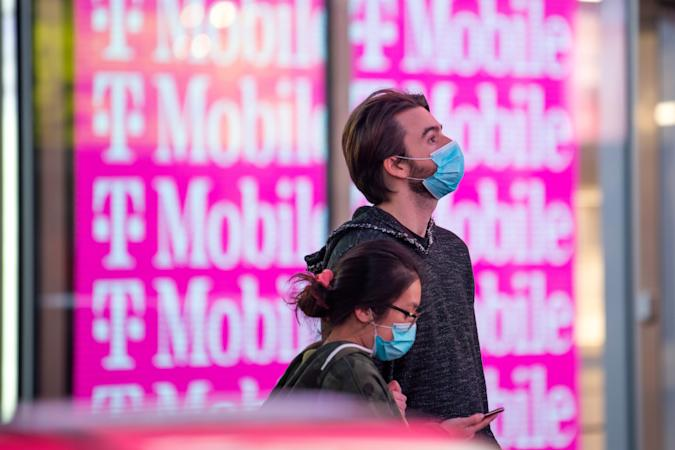 NEW YORK, NEW YORK - MAY 17: Two people wearing masks stand in front of the T-Mobile store in Times Square amid the coronavirus pandemic on May 17, 2020 in New York City. COVID-19 has spread to most countries around the world, claiming over 316,000 lives with over 4.8 million cases. (Photo by Alexi Rosenfeld/Getty Images)