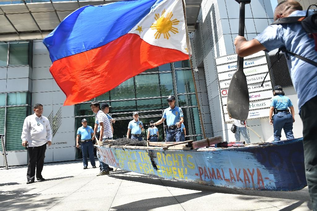 Fishermen and activists carry a wooden fishing boat during a protest outside the Chinese consulate in Manila ahead of a UN tribunal ruling on the legality of China's claims to the South China Sea (AFP Photo/Ted Aljibe)