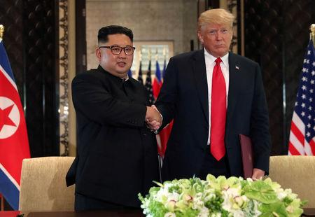 FILE PHOTO: U.S. President Donald Trump shakes hands with North Korea's leader Kim Jong Un after they signed documents that acknowledged the progress of the talks and pledge to keep momentum going, after their summit at the Capella Hotel on Sentosa island in Singapore June 12, 2018. REUTERS/Jonathan Ernst/File Photo
