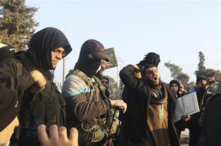 Fighters from the Islamic State in Iraq and the Levant (ISIL) try to calm civilians demonstrating against the rebel infighting in Aleppo