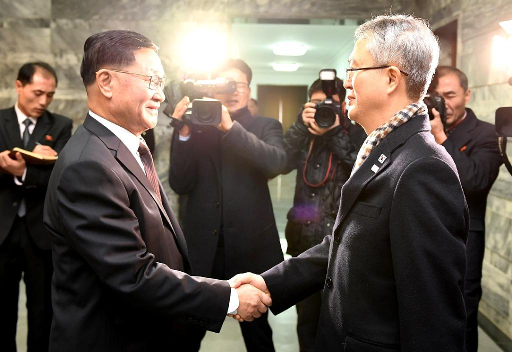 This handout photo provided by the South Korean Unification Ministry shows North Korea's chief delegate Kwon Hyok-Bong (L) greeting South Korea's chief delegate Lee Woo-Sung (R) (AFP Photo/Handout)