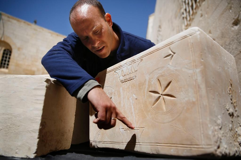 Israeli archeologist Eitan Klein of the Antiquities Theft Prevention Unit points at an engraved detail on one of the 11 ancient coffins containing Jewish bones from the Second Temple period after they were recovered from thieves, on March 31, 2014