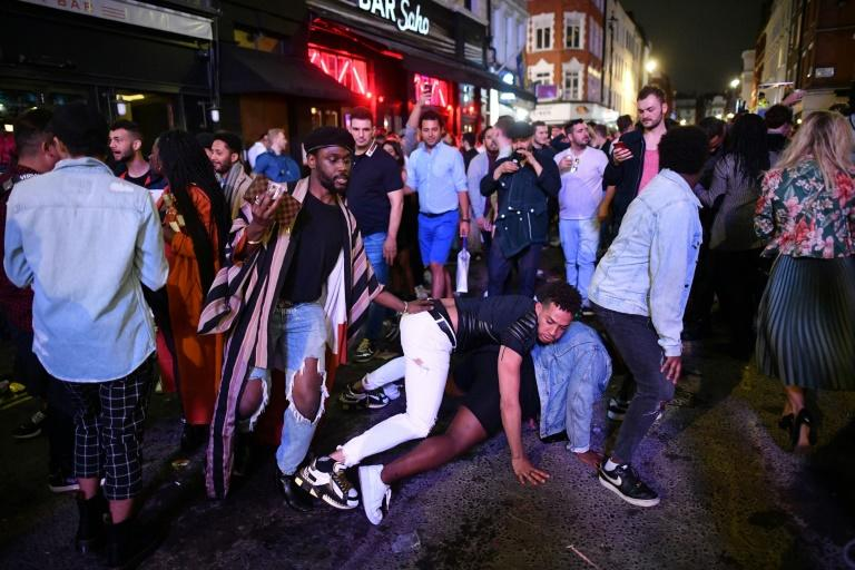 Revellers danced in the street the night pubs finally reopened (AFP Photo/JUSTIN TALLIS)
