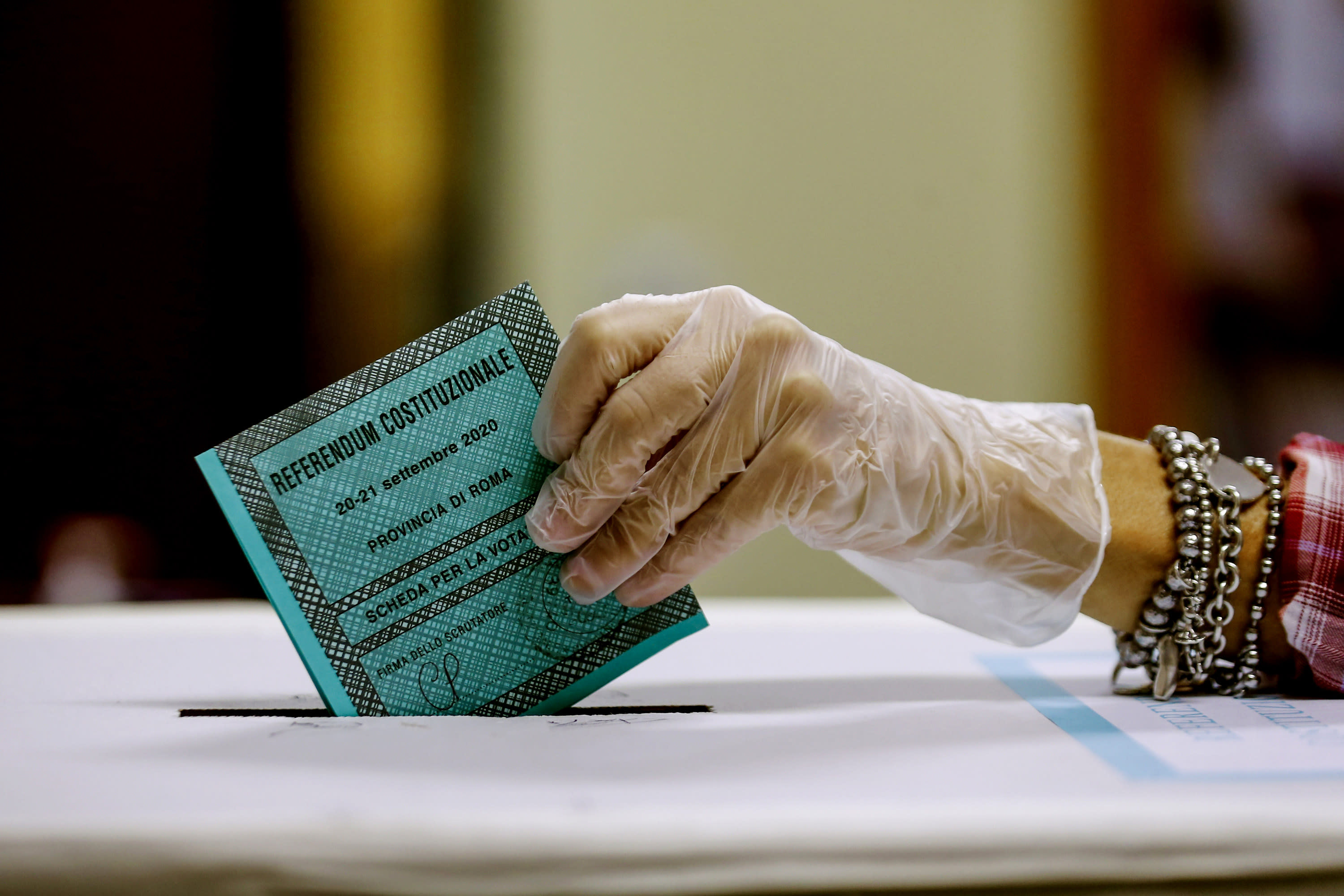 A woman casts her ballot at a polling station, in Rome, Monday, Sept. 21, 2020. On Sunday and Monday Italians are called to vote nationwide in a referendum to confirm a historical change to the country's constitution to drastically reduce the number of Members of Parliament from 945 to 600. Eighteen million of Italian citizens will also vote on Sunday and Monday to renew local governors in seven regions, along with mayors in approximately 1,000 cities. (Cecilia Fabiano/Lapresse via AP)