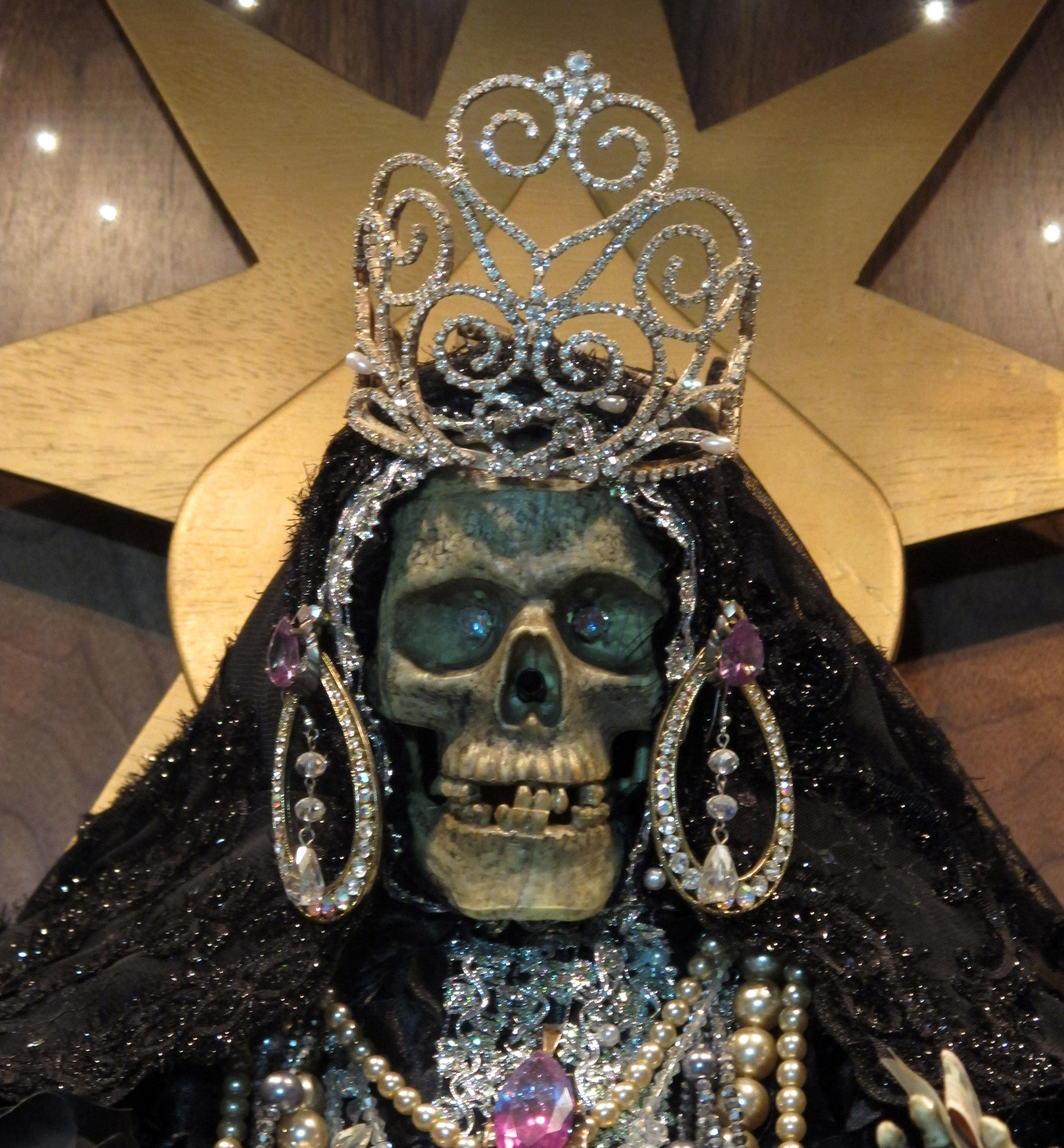 In this Feb. 12, 2013 photo, a statue of La Sante Muerte from an altar run by Arely Vazquez Gonzalez, a Mexican immigrant and transgender woman, is shown at inside a Queens, NY apartment. La Santa Muerte, an underworld saint most recently associated with the violent drug trade in Mexico, now is spreading throughout the U.S. among a new group of followers ranging from immigrant small business owners to artists and gay activists. In addition to showing up at drug crime scenes, the once-underground icon has been spotted on passion candles in Richmond, Va. grocery stores. The folk saint's image can be seen inside New York City apartments, in Minneapolis religious shops and during art shows in Tucson, Ariz. (AP Photo/Russell Contreras)