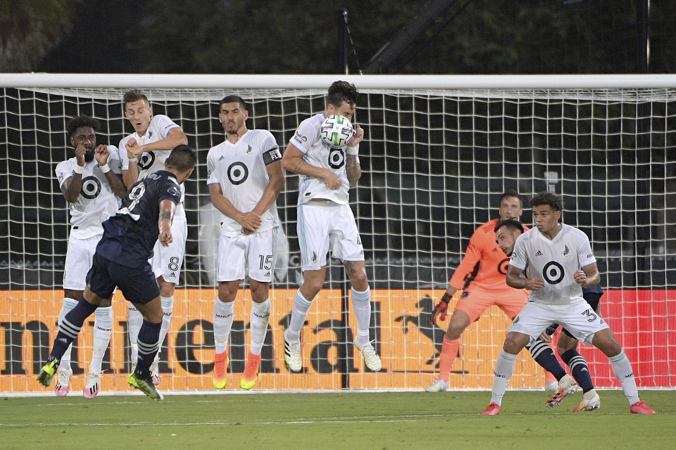 Minnesota United defender Jose Aja, center, gets hit in the face by the ball on a penalty kick by Sporting KC forward Alan Pulido (9) during the first half of an MLS soccer match, Sunday, July 12, 2020, in Kissimmee, Fla. (AP Photo/Phelan M. Ebenhack)