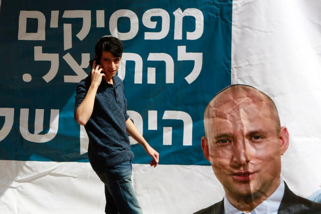An Israeli man walks past an election campaign poster, of Israeli Economy Minister and head of the far-right Jewish Home party Naftali Bennett (AFP Photo/Gali Tibbon)