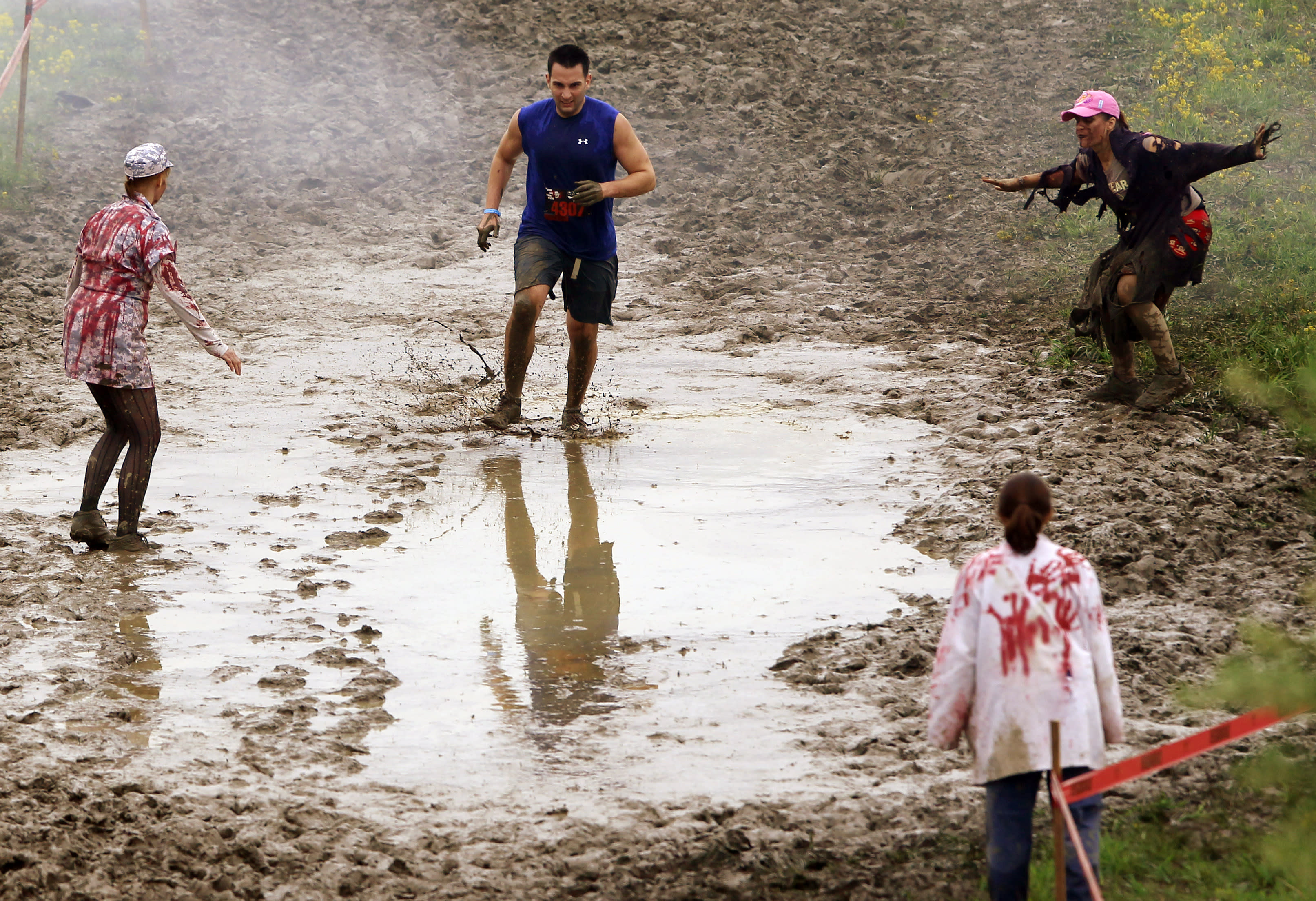 """Zombies chase runners on the """"Run for Your Lives"""" 5K obstacle course race in Amesbury, Massachusetts May 5, 2012. Runners face man-made and natural obstacles on the course, while being chased by zombies, who try to take """"health"""" flags off the runners belts. REUTERS/Brian Snyder"""
