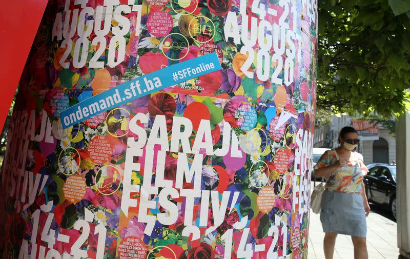 A woman wearing a protective mask walks past the Sarajevo Film Festival posters in Sarajevo