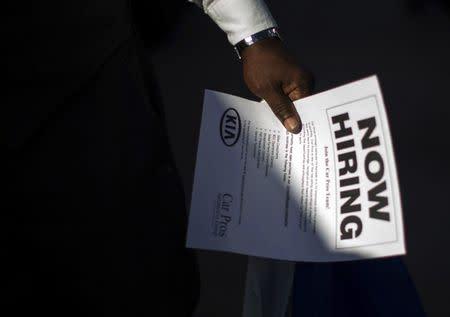 Man holds a leaflet at a military veterans' job fair in Carson