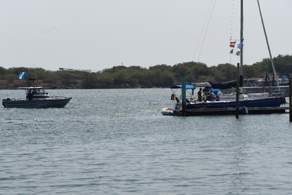 "An army boat approaches the ""abortion ship"" of the Dutch organization Women on Waves at the Pez Vela Marina in the port of San Jose, Escuintla department, 120 km south of Guatemala City, on February 23, 2017 (AFP Photo/JOHAN ORDONEZ)"