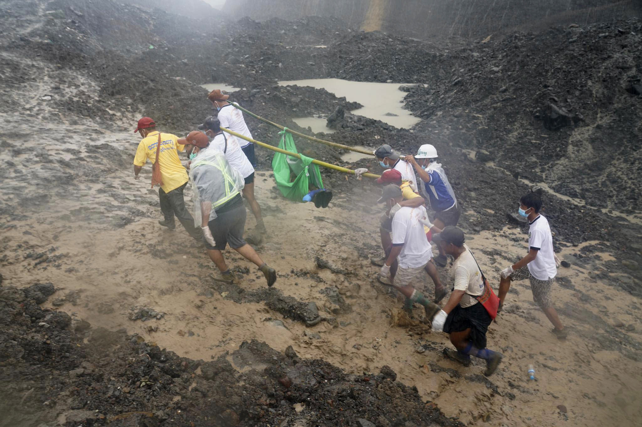 People use poles to carry a recovered body shrouded in green plastic Friday, July 3, 2020 in Hpakant, Kachin State, Myanmar. More than 100 people were killed Thursday in a landslide at a jade mine in northern Myanmar, the worst in a series of deadly accidents at such sites in recent years. (AP Photo/Zaw Moe Htet)