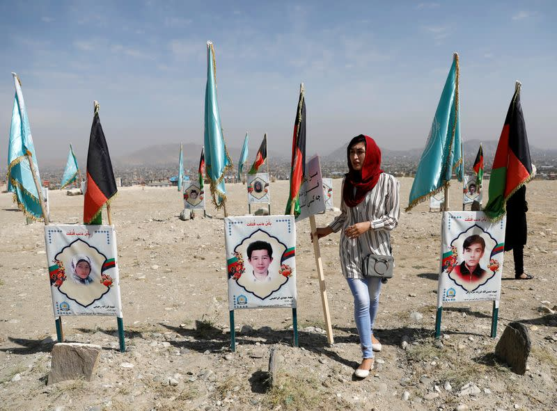A woman walks at a graveyard of the victims who were killed in a suicide attack in an educational centre two years ago, in Kabul