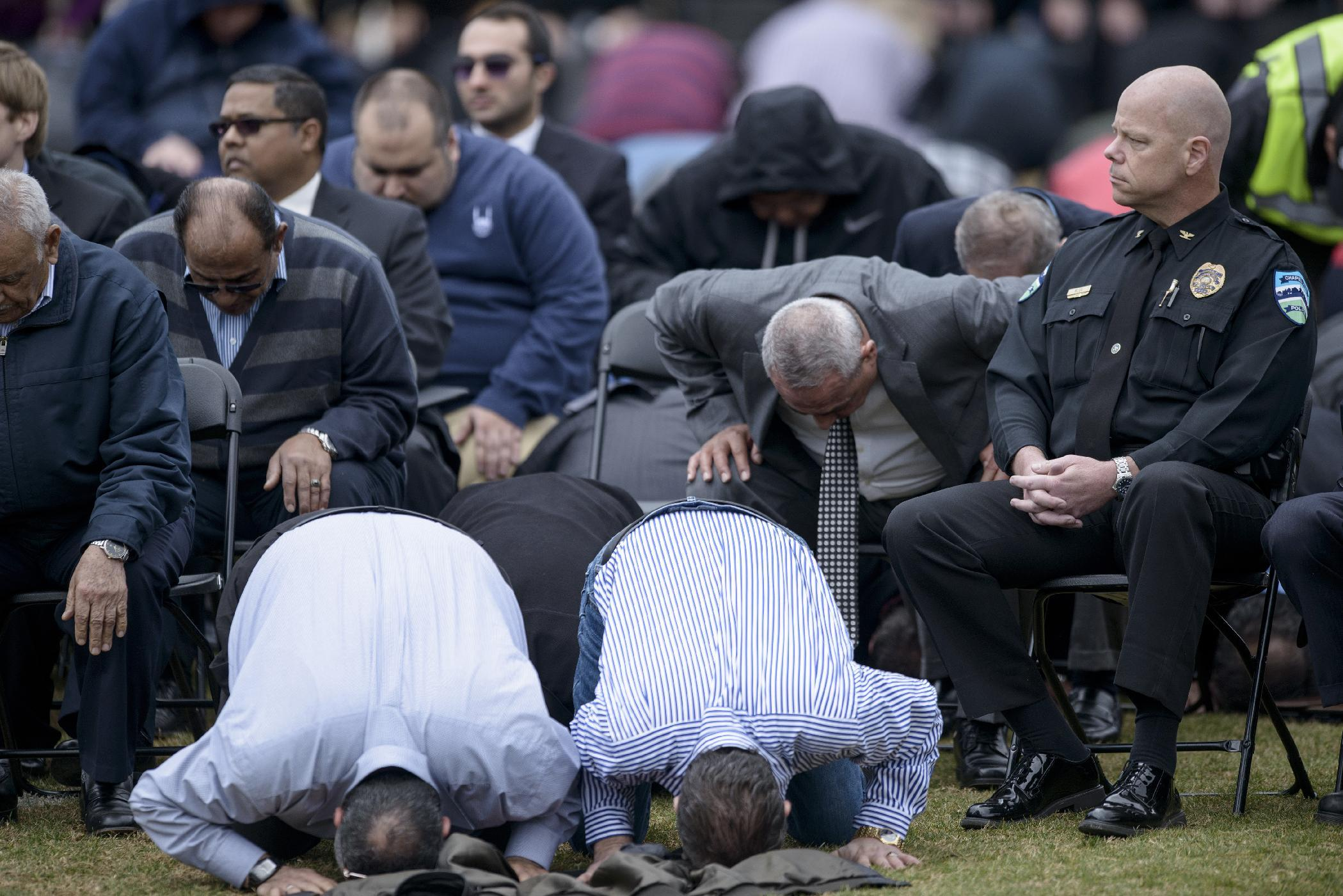 Chapel Hill Police Chief Chris Blue (R) listens as people pray during a service in a soccer field near the Islamic Association of Raleigh February 12, 2015, in Raleigh, North Carolina (AFP Photo/Brendan Smialowski)