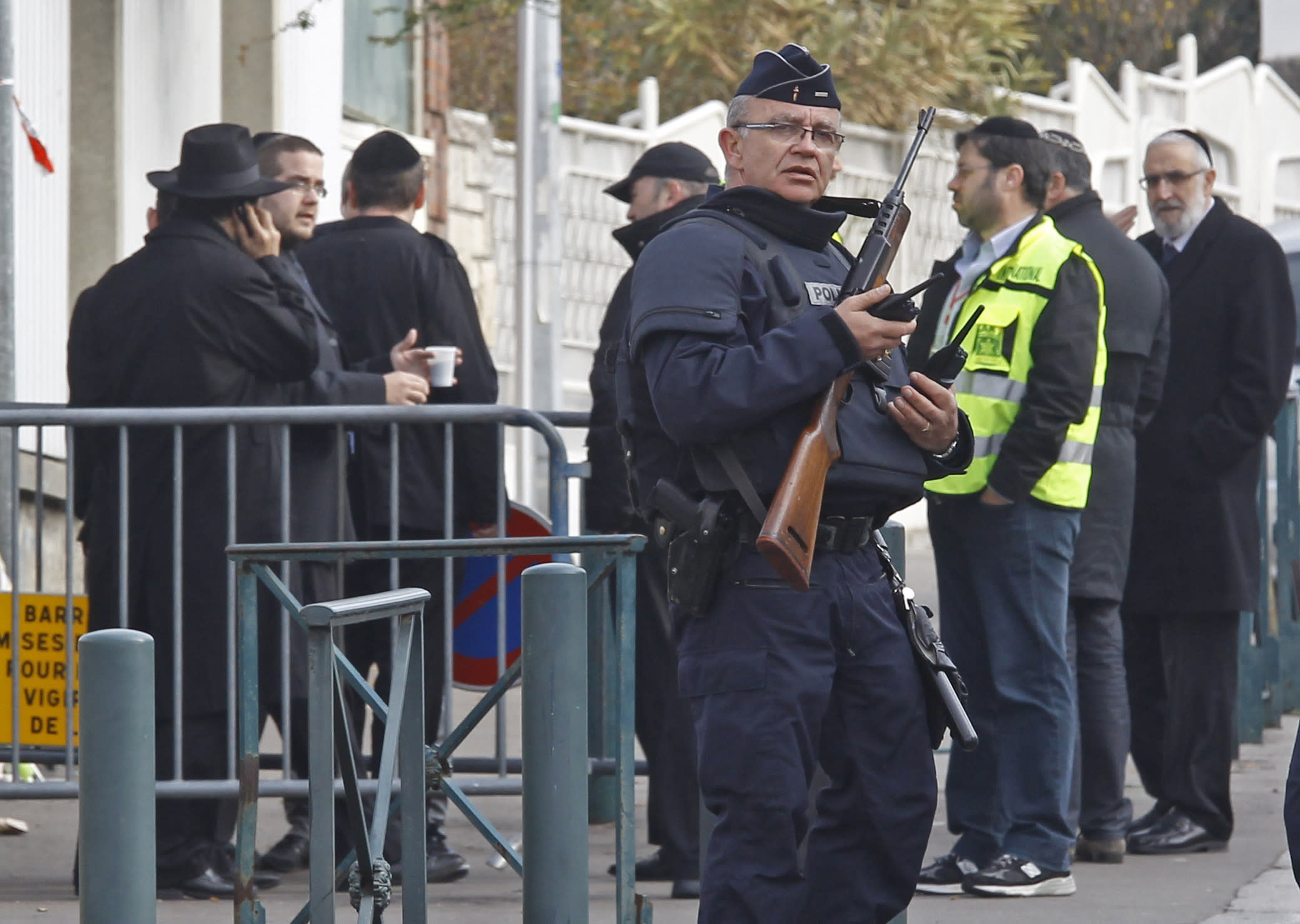 An armed police officer stands guard at the entrance of the Ozar Hatorah Jewish school where a gunman opened fire killing four people in Toulouse, southwestern France, Tuesday, March 20, 2012. A father and his two sons were among four people who died Monday when a gunman opened fire in front of a Jewish school in a city in southwest France, the Toulouse prosecutor said Monday.(AP Photo/Remy de la Mauviniere)