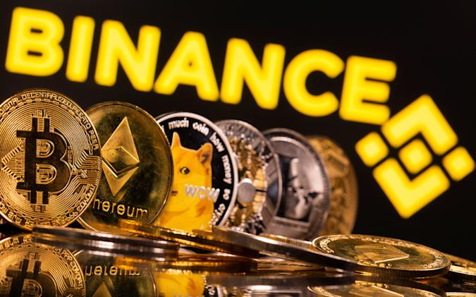 Representations of cryptocurrencies Bitcoin, Ethereum, DogeCoin, Ripple, and Litecoin are seen in front of a displayed Binance logo in this illustration taken, June 28, 2021. REUTERS/Dado Ruvic/Illustration