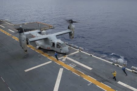 A landing signalman directs an Osprey aircraft to land on flight deck of the amphibious assault ship USS Bonhomme Richard (LHD 6), flagship of the Bonhomme Richard Expeditionary Strike Group, operating in the South China Sea on October 6, 2016. Courtesy David Holmes/U.S. Navy/Handout via REUTERS