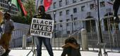 A young Black Lives Matter protester sits at the steps of the Hall of Justice in downtown Los Angeles. (AP)