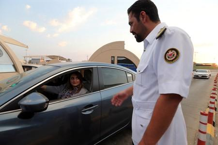 Immigration officer assists a Saudi woman at a Bahrain-Saudi border checkpoint