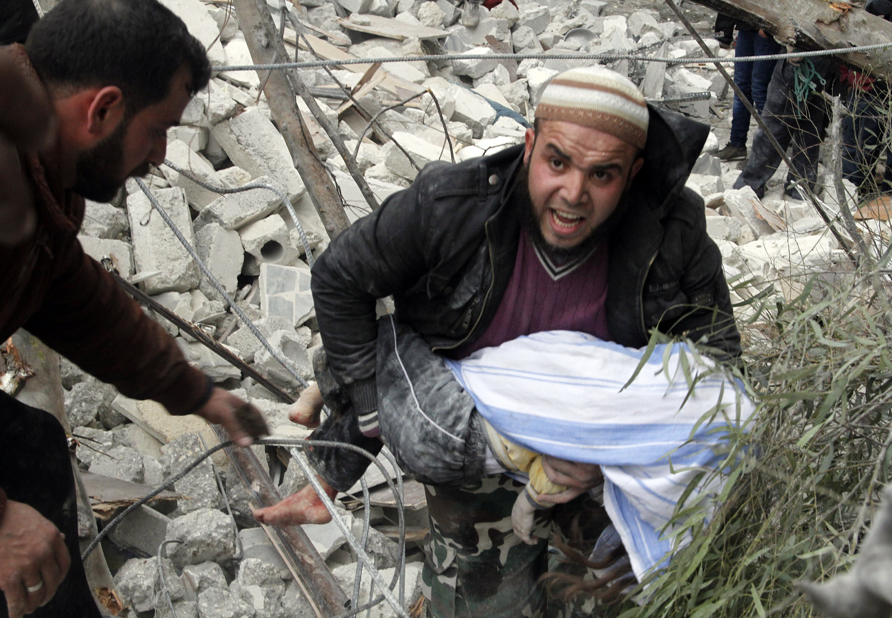 A Syrian man carries a child's body after a government airstrike hit the neighborhood of Ansari, in Aleppo, Syria, Sunday, Feb. 3, 2013. The Britain-based activist group Syrian Observatory for Human Rights, which opposes the regime, said government troops bombarded a building in Aleppo's rebel-held neighborhood of Eastern Ansari that killed over 10 people, including at least five children. (AP Photo/Abdullah al-Yassin)