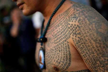 A devotee attends the religious tattoo festival at Wat Bang Phra, where they come to recharge the power of their sacred tattoos, in Nakhon Pathom province, Thailand, March 11, 2017. REUTERS/Jorge Silva