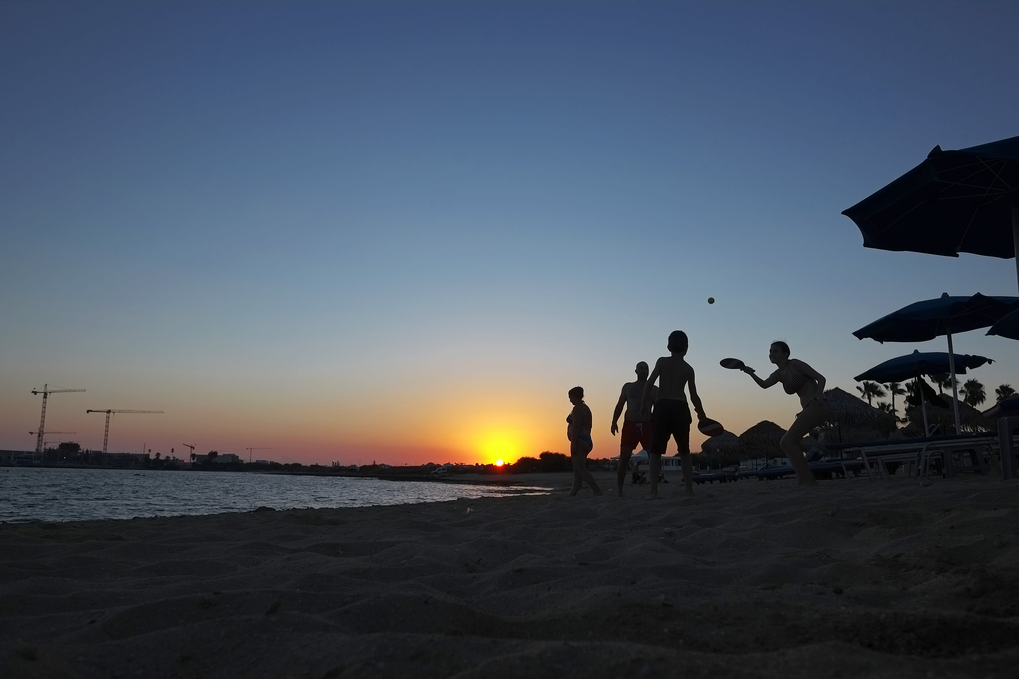 People play beach racket at the beach during sunset in coastal resort of Ayia Napa in the eastern Mediterranean island of Cyprus, Saturday, Aug. 22, 2020. Health Minister Constantinos Ioannou has extended until Jan. 15, 2021, a ban on outdoor festivals, concerts and exhibitions in places without seating where social distancing rules can't be enforced. (AP Photo/Petros Karadjias)