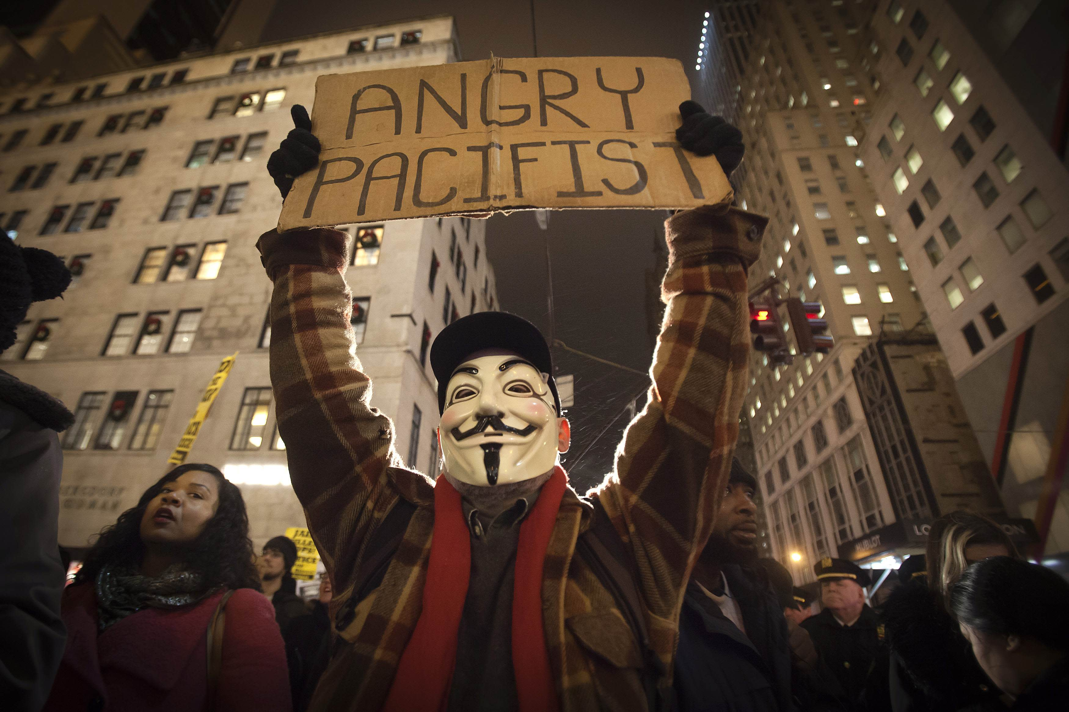 A demonstrator wearing a Guy Fawkes mask walks up 6th Ave as he protests against the police in the Manhattan borough of New York December 23, 2014. Mayor Bill de Blasio's attempts to soothe a city dismayed by the slaying of two officers were further rebuffed on Tuesday as protesters defied his call to suspend what have become regular demonstrations over excessive police force. REUTERS/Carlo Allegri (UNITED STATES - Tags: CIVIL UNREST CRIME LAW TPX IMAGES OF THE DAY)