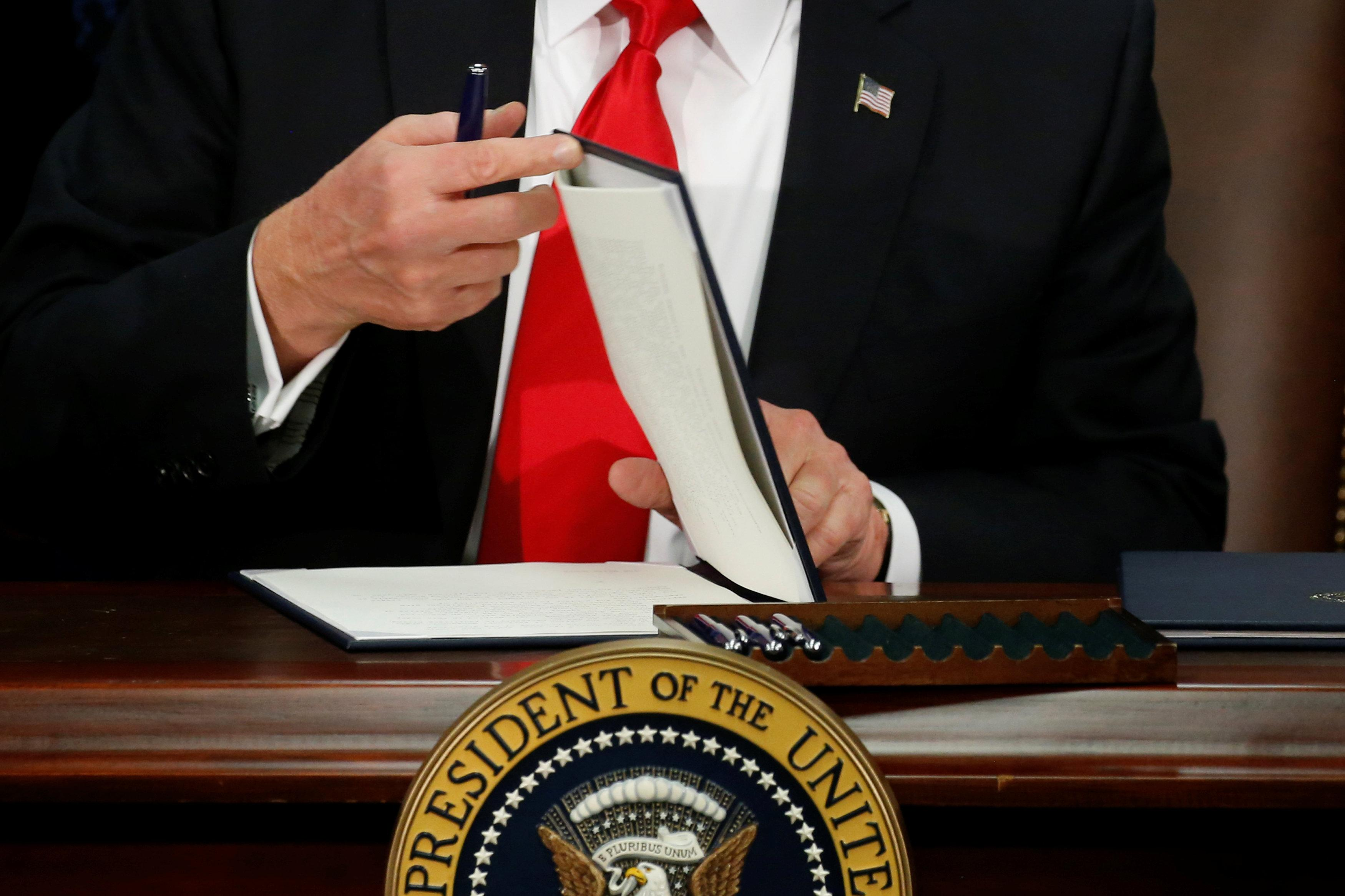 U.S. President Donald Trump prepares to sign an executive order at Homeland Security headquarters in Washington, U.S., January 25, 2017. REUTERS/Jonathan Ernst