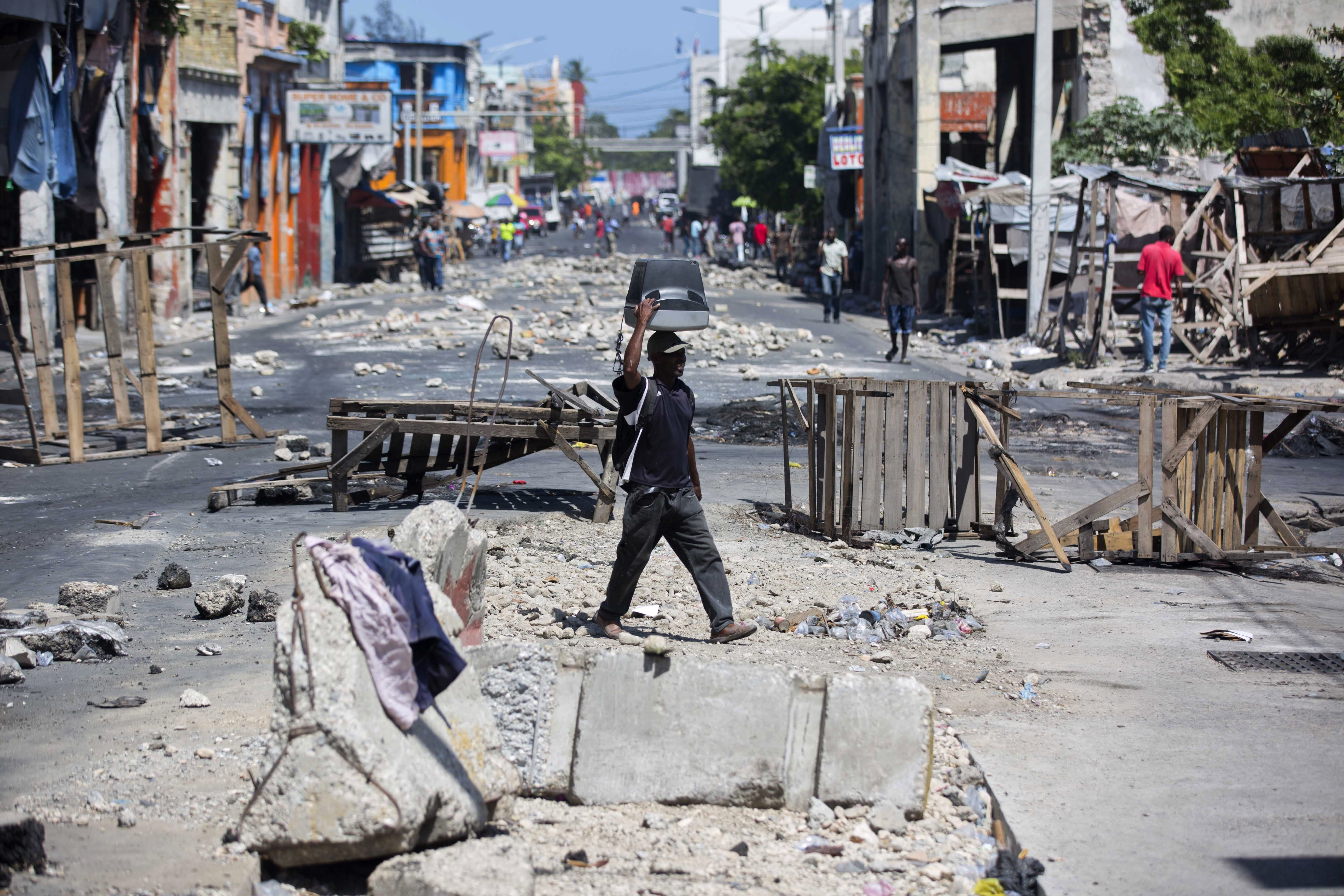 <p>A man balances a TV monitor on his head as he walks through roadblocks set up by anti-government protesters during a general strike in Port-au-Prince, Haiti, Monday, July 9, 2018. (Photo: Dieu Nalio Chery/AP) </p>