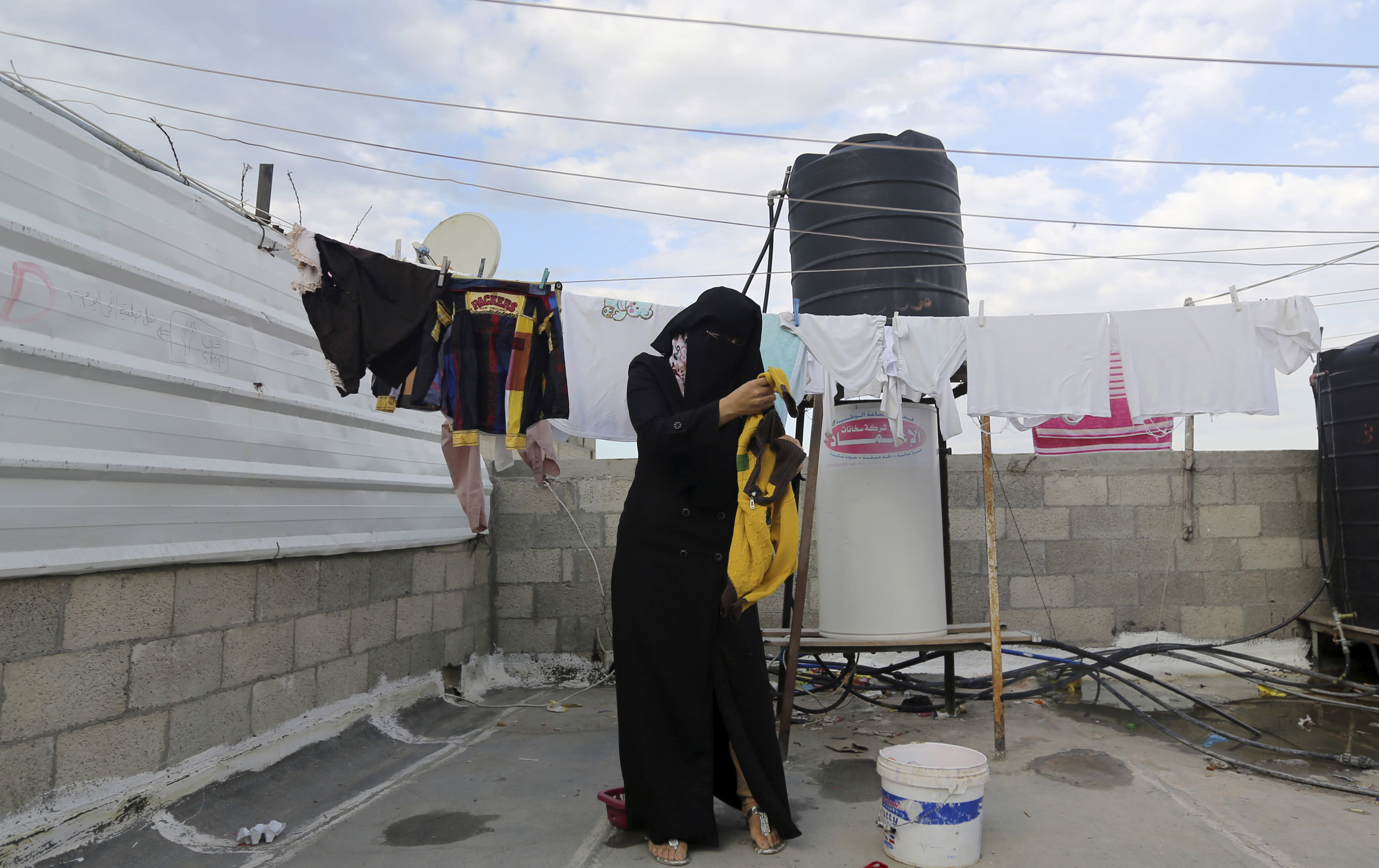 In this Tuesday, March 11, 2014 photo, Minatullah Zeitouniya, 29, hangs laundry to dry on the roof of the apartment building she and her family live in Gaza City in the northern Gaza Strip. Gaza's Hamas rulers have been hit by the worst economic crisis since seizing the territory seven years ago and face growing discontent, even among core supporters, because there's no sign of relief from a blockade enforced not only by Israel but also by a suddenly hostile Egypt. (AP Photo/Hatem Moussa)