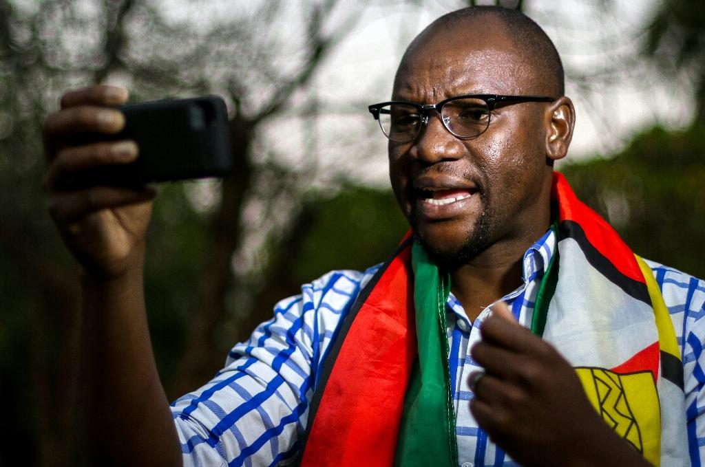 Zimbabwean cleric Evan Mawarire, pictured in May 2016, wrapped in the Zimbabwean National flag, recording an instalment of his #ThisFlag video series, in which he decries the government's failure to provide basic services