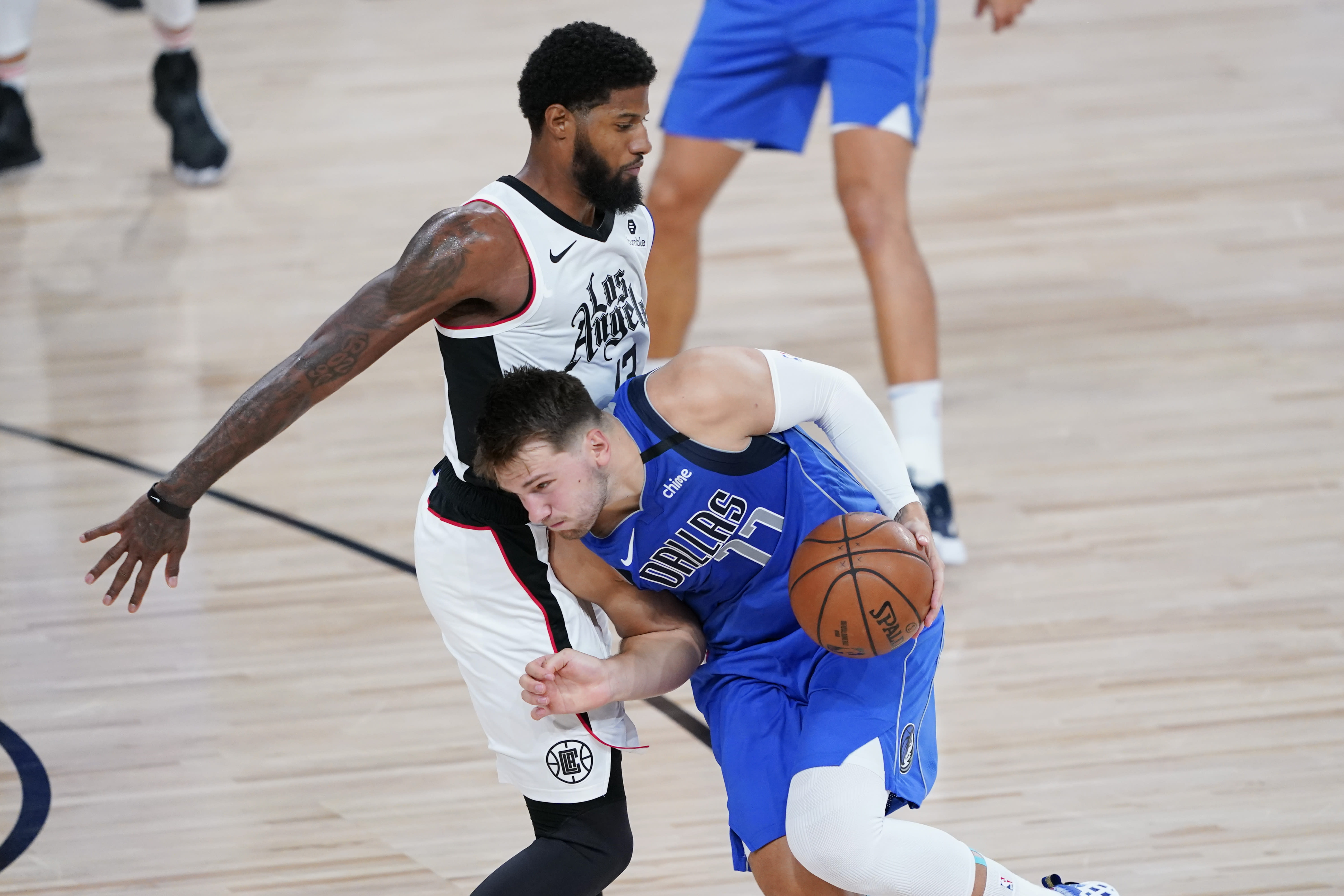 Dallas Mavericks' Luka Doncic (77) drives against Los Angeles Clippers' Paul George (13) during the first half of an NBA basketball first round playoff game Friday, Aug. 21, 2020, in Lake Buena Vista, Fla. (AP Photo/Ashley Landis, Pool)