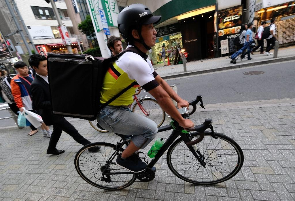 While meal delivery service UberEATS has been a hit in Tokyo since arriving in 2016, Japan's sharing economy is a fraction of the size of markets in Europe, the US and China (AFP Photo/Kazuhiro NOGI)