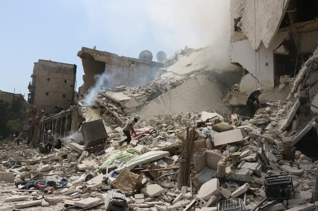 Syrian rescue workers search for victims through the rubble of a building destroyed during a reported barrel bomb attack in a rebel-held neighbourhood in eastern Aleppo on August 27, 2016 (AFP Photo/Thaer Mohammed)