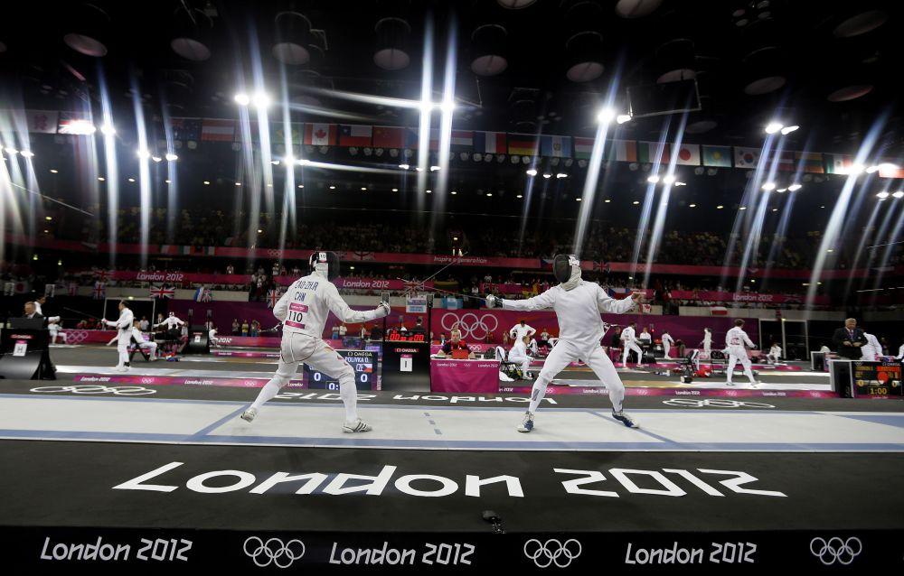 ARCHIVO - En esta foto del 11 de agosto del 2012, el chino Cao Zhongrong, izquierda, y Ondrej Polivka, de la República Checa, compiten durante la sección de esgrima en el pentatlón  moderno en las Olimpiadas de Londres. Eliminar un deporte de las Olimpiadas es una de las tareas más espinosas del COI. Luego de meses de evaluaciones, la decisión se producirá el martes, 12 de febrero del 2013. Ell pentatlón parece el más en peligro. (Foto AP/Kirsty Wigglesworth)