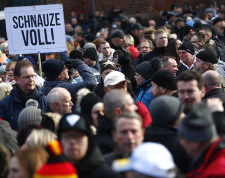 """People attend a demonstration against migrants in Cottbus, Germany February 3, 2018. Sign reads """"Fed up!"""". REUTERS/Hannibal Hanschke"""