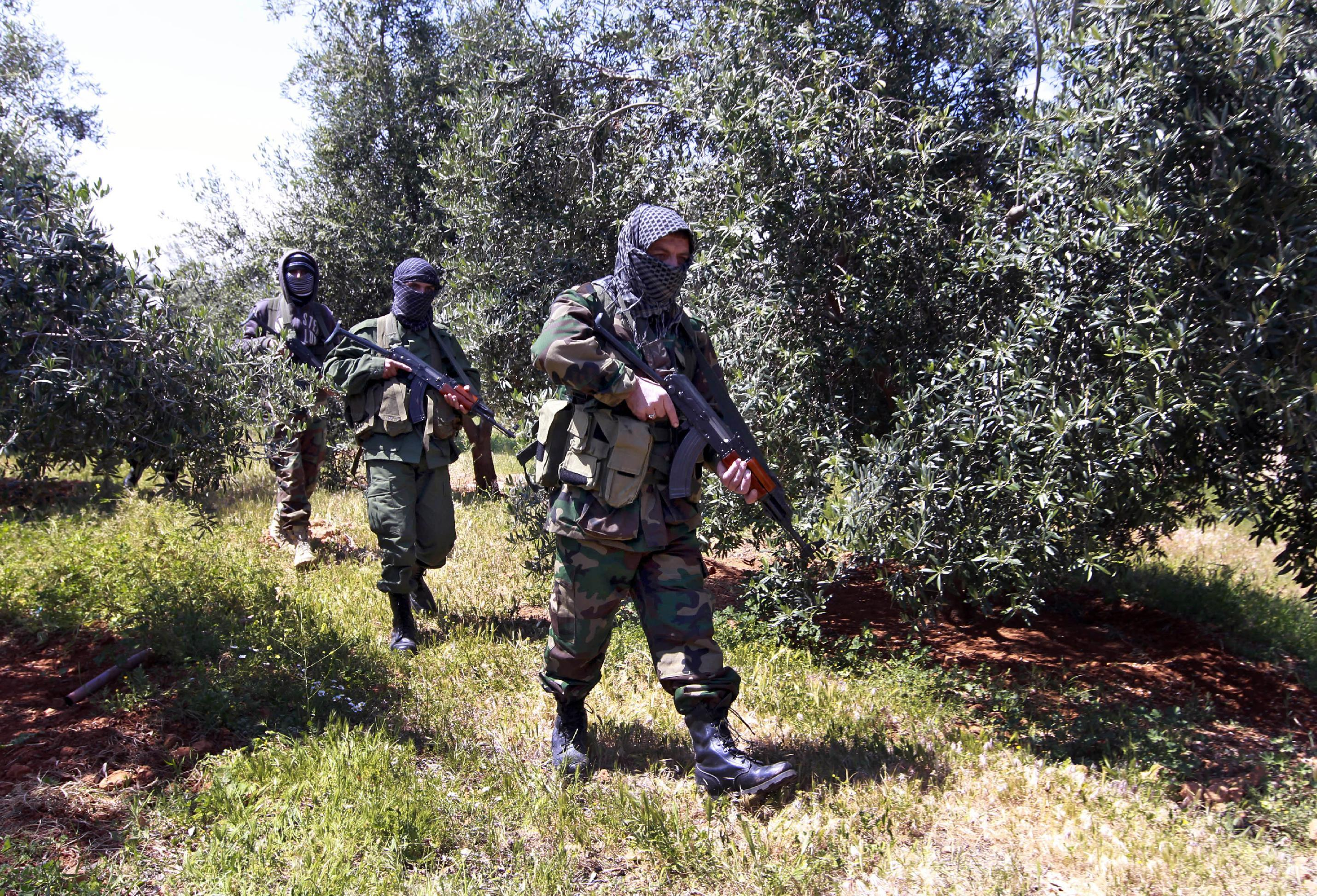 In this Friday, April 12, 2013 photo, Hezbollah fighters walk through a field at the Lebanon-Syria border, near the northeastern Lebanese town of al-Qasr, Lebanon. The Shiite group has sent hundreds of its fighters into Syria to shore up President Bashar Assad's overstretched troops, helping them gain ground around the capital, Damascus, and near the Lebanese border. But with its own casualties mounting in a civil war that activists say has killed more than 150,000 people in three years, officials say Hezbollah has turned to a variety of new tactics - including complicated commando operations - to hunt down rebels and opposition commanders. (AP Photo/Bilal Hussein)