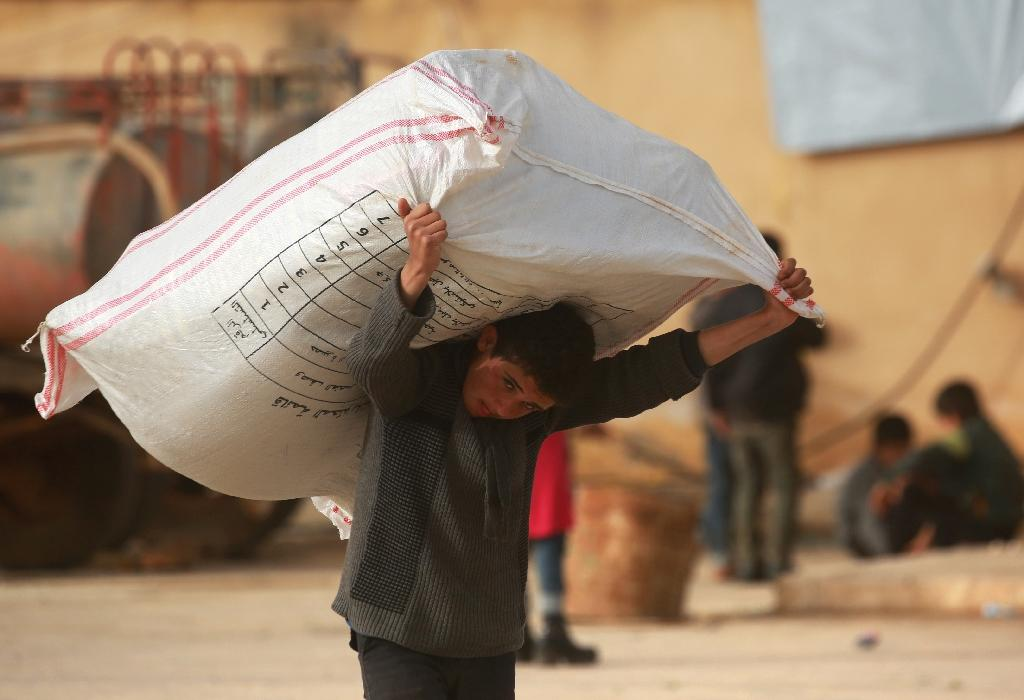 A Syrian boy carries a sack on March 22, 2018 at a make-shift camp near Manbij for people displaced by a Turkish offensive on the Afrin area (AFP Photo/Delil SOULEIMAN)