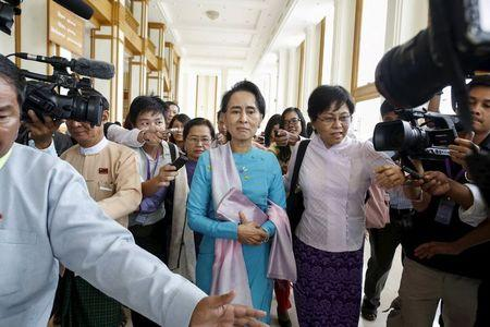 Myanmar pro-democracy and opposition leader Aung San Suu Kyi talks to the media as she attends a Parliament meeting at the Lower House of Parliament in Naypyitaw