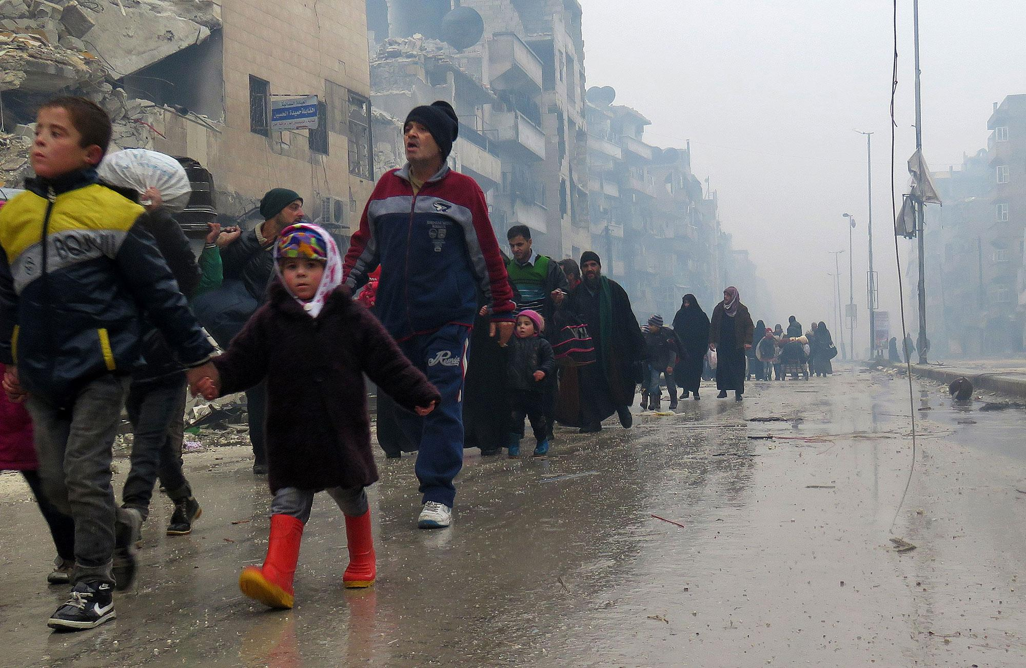 <p>Syrian residents, fleeing violence in the restive Bustan al-Qasr neighbourhood, arrive in Aleppo's Fardos neighbourhood on December 13, 2016, after regime troops retook the area from rebel fighters. Syrian rebels withdrew from six more neighbourhoods in their one-time bastion of east Aleppo in the face of advancing government troops, the Syrian Observatory for Human Rights said. (Stringer/AFP/Getty Images) </p>
